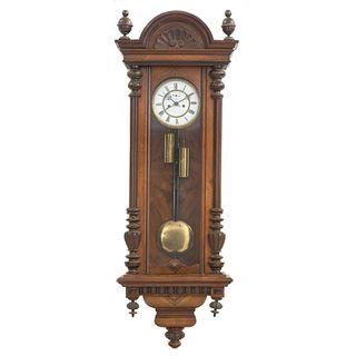Reloj de pared. Francia. SXX. En talla de madera de nogal. Mecanismo de cuerda y péndulo. 120 x 44 x 20 cm