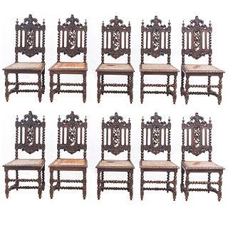 Lote de 10 sillas. Francia. SXX. Estilo Enrique II. En talla de madera de roble. Con respaldos semiabiertos, asientos de bejuco.