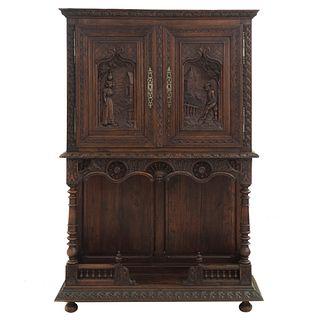 Gabinete. Francia. SXX. Estilo Bretón. En talla de madera de roble. Con repisa inferior, puertas superiores y soportes. 177x120x43 cm