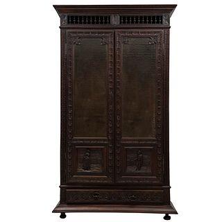 Librero. Francia. SXX. Estilo Bretón. En talla de madera de roble. Con 2 puertas abatibles con vidrio y cajón. 220 x 128 x 51 cm