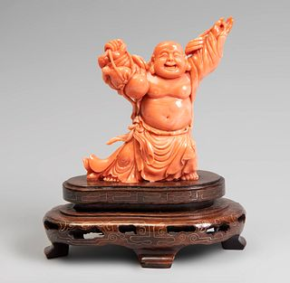 Smiling Buddha. China, 20th century. Coral. Carved wooden base. Weight: 478 gr (with base).