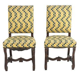 Par de sillas. SXX. Talla en madera. Con respaldos cerrados y asientos en tapicería geométrica color verde y beige.