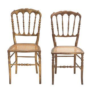 Par de sillas. SXX. Elaboradas en madera dorada. Con respaldos semiabiertos y asientos de bejuco.