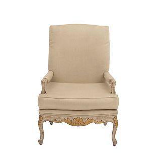 Sillón. SXX. Talla en madera. Con respaldo cerrado y asiento en tapicería color beige, fustes semicurvos y soportes tipo cabriolé.