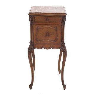 Mesa de noche. Francia. SXX. Estilo Luis XV. En talla de madera de nogal. Cubierta de mármol, cajón y puerta. 85 x 40 x 39 cm.