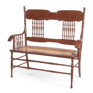 Love seat. SXX. Estilo Early American. Elaborado en madera tallada. Respaldo con barandillas, asiento de bejuco.