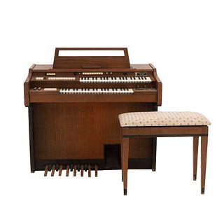 Piano eléctrico. Estados Unidos. SXX. Elaborado en madera. Con banco. Marca Gulbransen. Aplicaciones de metal dorado.