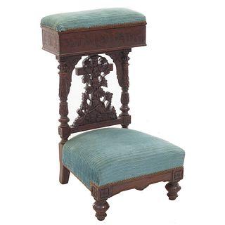 Reclinatorio. Francia. SXX. En talla de madera de nogal. Tapicería en color azul, con cubierta abatible y soportes tipo.