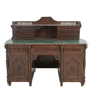 Escritorio. Ca. 1900 En talla de madera. A 2 cuerpos y 2 vistas. Con cubierta irregular color verde, seis cajones en la parte superior.
