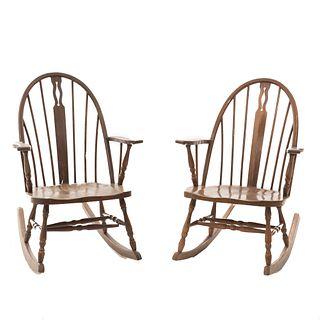 """Par de mecedoras. SXX. Elaboradas en madera. Con respaldos semiabiertos, chambranas en """"H"""" y soportes en """"ll""""."""