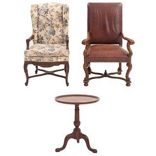 2 sillones y mesa auxiliar. SXX. Elaborados en madera. Un sillón con tapicería de piel color marrón y otro de tela.