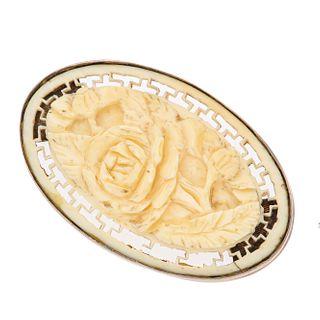 Prendedor con hueso y plata paladio. Diseño floral. Peso: 8.2 g.