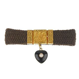 A mid 19th century gold split pearl memorial hair bracelet. The scrolling foliate monogram panel, su