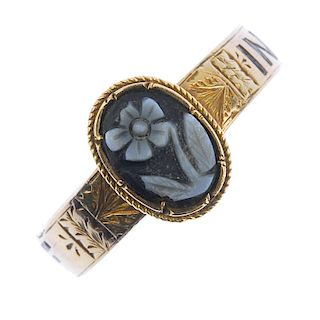 A mid Victorian gold memorial ring. The central oval onyx panel carved to depict a forget-me-not to
