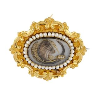 A mid Victorian gold split pearl memorial brooch. The oval arranged hair panel, within a split pearl