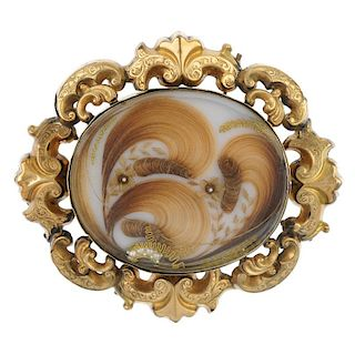 A late 19th century memorial brooch. The sculpted hair and split pearl panel, with photograph revers