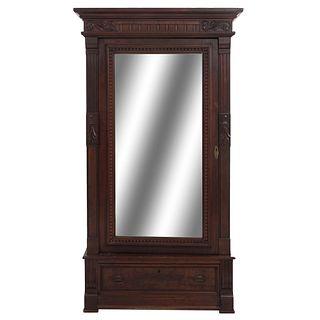 Armario. SXX. Elaborado en madera. Puerta con espejo biselado, cajón y entrepaños internos. Decorado con elementos orgánicos.