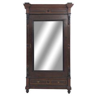 Armario. SXX. Elaborado en madera. Puerta con espejo biselado, cajón y soportes tipo carrete. Decorado con molduras.
