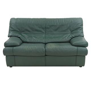 Love seat. SXX. Estructura de madera con recubrimiento en tapicería tipo piel color verde. Con respaldo cerrado y asientos con cojines.
