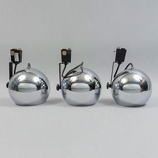 Lote de 3 lámparas para riel. SXX. Estructura metálica. Para una luz cada una. Incluyen riel. 22 cm de diámetro cada una.