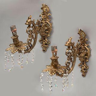 Par de arbotantes.  SXX. Elaborados en bronce. Diseño garigoleado con hilos colgantes de cristal. Para 1 luz. 27 cm de longitud.
