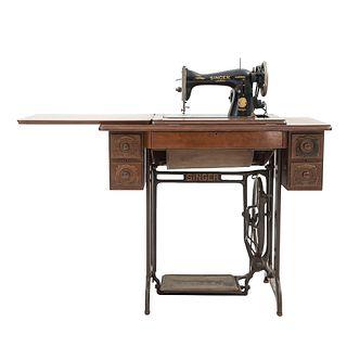 Máquina de coser. SXX. Elaborada en metal. Marca Singer. Mueble de madera con 5 cajones. Decorada con elementos florales.