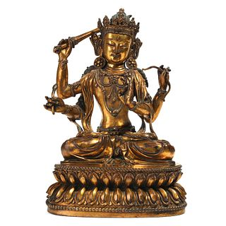 A GILT BRONZE FOUR-ARMED SEATED BODHISATTVA