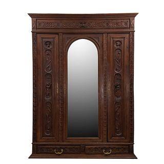 ARMARIO. FRANCIA, SXX. Estilo BRETÓN. Elaborado en madera de roble. Con 3 puertas abatibles, una con espejo de luna irregular.