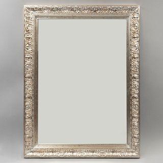Espejo. SXX. Diseño rectangular. Elaborado en madera plateada. Con luna rectangular. Decorado con elementos orgánicos. 83 x 63 cm