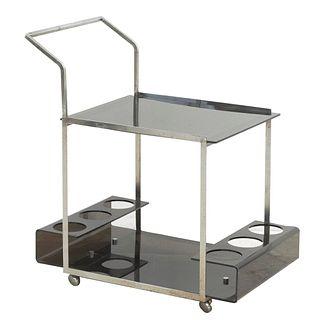 Carrito de servicio. SXX. Elaborado en metal cromado y acrílico. A 2 pisos. Soportes con ruedas.