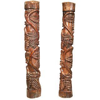 Par de columnas. México, sXX. Elaboradas en madera tallada y entintada. Decoradas con hojas de parra, vides, acantos.