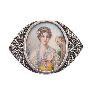 Prendedor con miniatura pintada a mano representando a una dama. Bisel en plata .800 con marquesitas. Peso: 16.2 g.