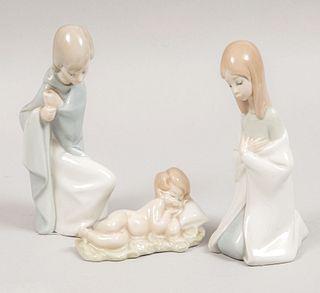 Virgen María, san José y Niño Jesús en pesebre. España, SXX. Elaboradas en porcelana Lladró. Acabado brillante. 15 cm de altura.