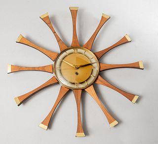 Reloj de pared. Francia, SXX. Elaborado en madera y metal dorado. Diseño solar. Mecanismo de cuerda. Carátula circular. 52 cm diámetro.