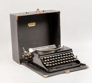 Máquina de escribir portátil. Estados Unidos, SXX. Marca Remington. Estructura de metal. Mecanismo manual. Con estuche.
