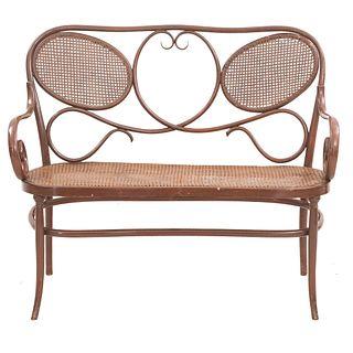 Love seat SXX. Estilo Austriaco. Elaborado en madera Respaldo semiabierto, asiento de bejuco tejido, chambrana oval y soportes lisos.