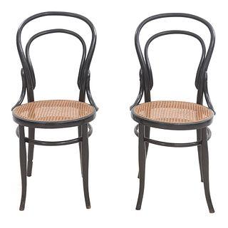 Par de sillas. SXX. Estilo Austriaco. Elaboradas en madera color negra. Respaldos semiabiertos, asientos de bejuco tejido.