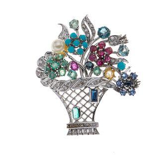 Prendedor con esmeraldas, turquesas, zafiros, diamantes y perla en plata paladio. 8 turquesas corte cabujón.