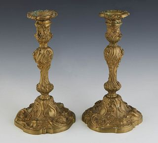 Pair of Gilt Bronze Candlesticks, c. 1900, the floriform bobeche atop a knopped support with relief floral decoration, on a like decorated scalloped b