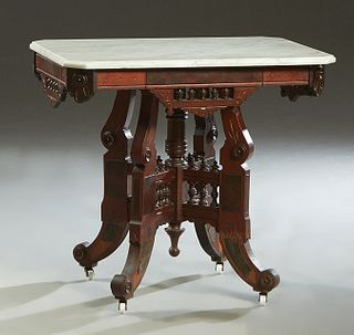 American Carved Walnut Marble Top Lamp Table, c. 1880, the ogee edge canted corner white marble top on a base with pierced spindled galleries on each