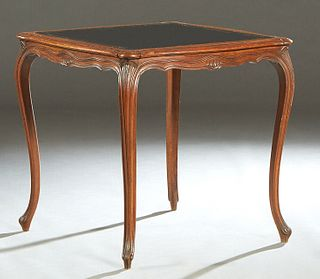 Louis XV Style Carved Mahogany Games Table, early 20th c., the stepped rounded edge bowed top with an inset gilt tooled black leather playing surface,