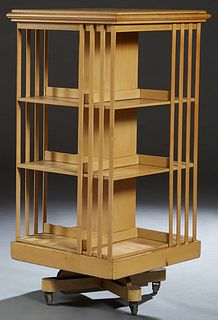 English Style Carved Blonde Mahogany Revolving Bookmill, early 20th c., the stepped square top over slatted shelves on all sides, to a square plinth,
