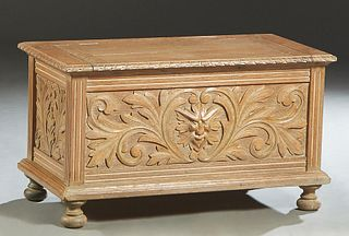 Continental Carved Oak Bedding Box, early 20th c., with leaf carved sides and a leaf and lion carved front panel, on a plinth base on bun feet, H.- 20