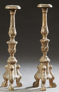 Pair of Italian Carved Giltwood Candle Sticks, 19th c., the candle cup on a tapered knopped support, to a tripodal sloping base on paw feet, H.- 17 in