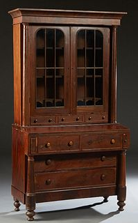 American Carved Mahogany Secretary Bookcase, 19th c., the ogee crown over double arched mullioned glazed doors, over two shallow drawers, flanked by t