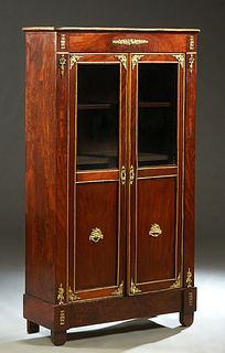 French Ormolu Mounted Carved Walnut Louis XVI Style Bookcase, early 20th c., the rounded corner top over double doors with glazed upper panels above w
