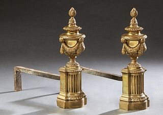 Pair of French Neo Classical Gilt Bronze and Iron Chenets, 19th c., with flame topped garland draped urns on reeded columnar supports, on stepped reli