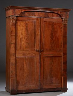 American Classical Carved Banded Mahogany Armoire, c. 1850, Philadelphia or New York, the stepped crown over an arched setback frieze atop double two