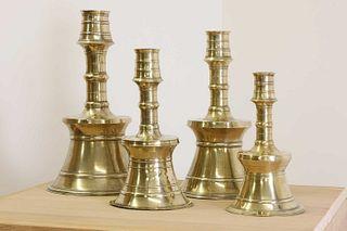 A graduated set of four bell-shaped brass candlesticks,