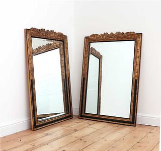A pair of ebonised and parcel-gilt mirrors,